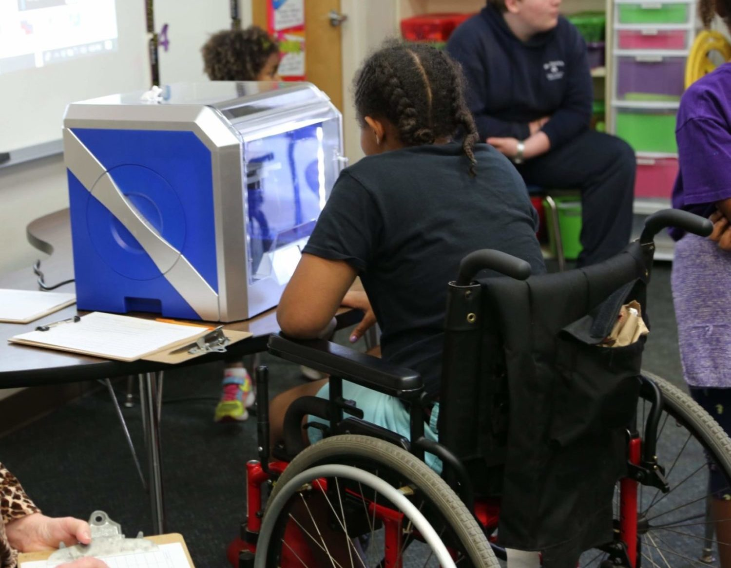 Young girl watching 3D printer from a wheelchair